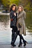 Två eleganta modemodeller som poserar i hösten, parkerar Arkivfoton