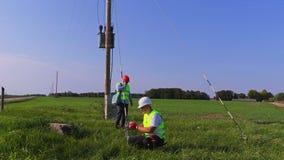 Två elektriker utför tekniskt underhåll för transformator stock video