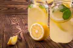 Två enorma exponeringsglas av en mojito med sidor för ny mintkaramell, mineralvatten, krossad is och citroner på en brun träbakgr Arkivfoto