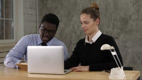 Två entreprenörer som sitter tillsammans att arbeta i ett kontorsskrivbord som sätter anmärkningar till anteckningsboken lager videofilmer