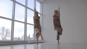 Två europeiska kvinnor som tillsammans gör yoga och den praktiserande örnen, poserar arkivfilmer