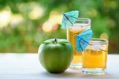 Två exponeringsglas av äppelmust med is och paraplyer Fotografering för Bildbyråer