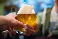 Två exponeringsglas av öl i hand ?lexponeringsglas som klirrar i st?ng eller bar royaltyfri fotografi
