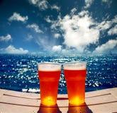 Två exponeringsglas av öl på en strand Arkivbilder