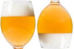 Två exponeringsglas av öl på en vit bakgrund Arkivfoton