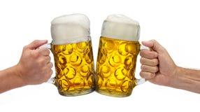 Två exponeringsglas av ölinnehavet i hand på Oktoberfest i Munich fotografering för bildbyråer