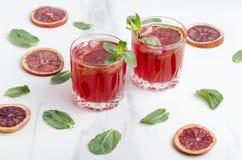 Två exponeringsglas av blodapelsinmargarite- och mintkaramellsidor, skivor av blodapelsinen på den vita tabellen fotografering för bildbyråer