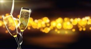 Två exponeringsglas av champagne över suddighet spots bakgrund Arkivbild
