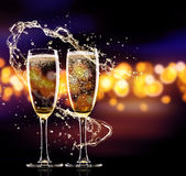 Två exponeringsglas av champagne över suddighet spots bakgrund Arkivfoton