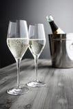 Två exponeringsglas av Champagne, flaska och kylare arkivbilder