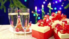 Två exponeringsglas av champagne med bubblanärbild mot bakgrunden av en tabell med oskarpa frukt och bränningstearinljus och herd