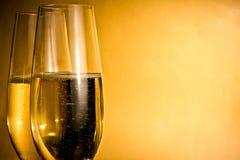 Två exponeringsglas av champagne med guld- bubblor och utrymme för text Royaltyfri Bild