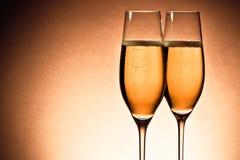 Två exponeringsglas av champagne med guld- bubblor och utrymme för text Royaltyfri Foto