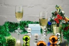Två exponeringsglas av champagne med julgåva och julbollar royaltyfri bild
