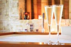 Två exponeringsglas av champagne nära bubbelpool som bakgrund är kan vykortet använda valentiner ro Arkivbild