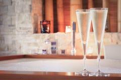 Två exponeringsglas av champagne nära bubbelpool som bakgrund är kan vykortet använda valentiner ro Royaltyfri Foto