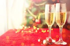 Två exponeringsglas av champagne nära härligt julträd Arkivbild