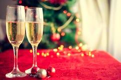 Två exponeringsglas av champagne nära härligt julträd Arkivfoto