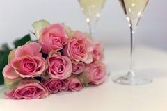 Två exponeringsglas av champagne och en bukett som göras av härliga ljusröda/rodnadrosa färgrosor royaltyfria foton