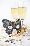 Två exponeringsglas av champagne och en maskera Arkivfoton
