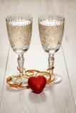 Två exponeringsglas av champagne och röd hjärta Arkivfoto