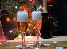 Två exponeringsglas av champagne på bakgrunden av champagne Julgran med julljus nytt år för jul Royaltyfri Foto