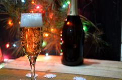 Två exponeringsglas av champagne på bakgrunden av champagne Julgran med julljus nytt år för jul Arkivbild