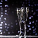 Två exponeringsglas av champagne på mörk bokehbakgrund Arkivfoton