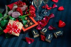 Två exponeringsglas av champagne, röda rosor, kronblad, gåvaask med det röda bandet, choklader och träförälskelseord på en svart  royaltyfria bilder