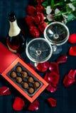 Två exponeringsglas av champagne, röda rosor, kronblad och choklader på en svart bakgrund arkivfoton