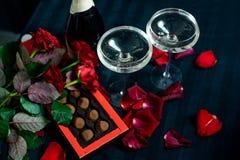 Två exponeringsglas av champagne, röda rosor, kronblad och choklader på en svart bakgrund royaltyfri foto
