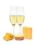 Två exponeringsglas av champagne, stearinljus och gulingrosen som isoleras på wh Royaltyfria Foton