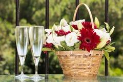 Två exponeringsglas av champange- och blommakorgen med det vanliga kuvertet Fotografering för Bildbyråer