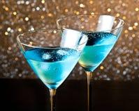Två exponeringsglas av den nya blåa coctailen med is på den wood tabellen arkivbild