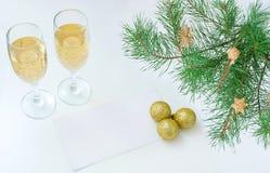 Två exponeringsglas av det vita tomma arket för champagne av papper Julgranfilialer och guld- bollar fotografering för bildbyråer