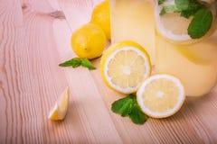 Två exponeringsglas av en mojito med den nya mintkaramellen, mineralvatten, krossad is och ljusa gula citroner på ett ljus - brun Royaltyfri Fotografi