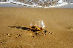 Två exponeringsglas av enkel malt för whisky på sanden tvättade sig vid waven arkivbild