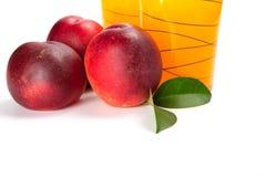 Två exponeringsglas av fruktsaft och nya persikor på vit bakgrund Arkivfoto
