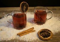 Två exponeringsglas av funderat vin i snön Arkivbild