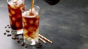 Två exponeringsglas av kallt kaffe på en mörk bakgrund I ett högväxt exponeringsglas med is häll svart kaffe långsam rörelse arkivfilmer