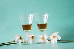 Två exponeringsglas av konjak- eller konjak- och vitpåskliljor på ett friläge Arkivfoto