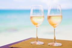 Två exponeringsglas av kylt vitt vin på tabellen nära Royaltyfri Foto
