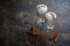 Två exponeringsglas av latte på en trälantlig tabell med kaffebönor och kanel Royaltyfri Bild