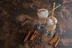 Två exponeringsglas av latte på en trälantlig tabell med kaffebönor och kanel Royaltyfri Foto