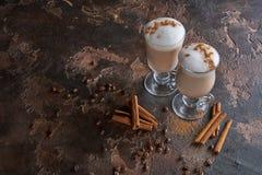Två exponeringsglas av latte på en trälantlig tabell med kaffebönor och kanel Arkivfoto
