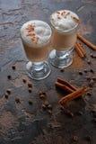 Två exponeringsglas av latte på en trätabell med kaffebönor och kanel Royaltyfria Bilder