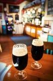 Två exponeringsglas av mörkt öl i en stång royaltyfri fotografi