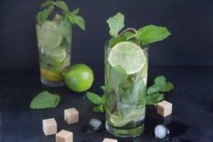 Två exponeringsglas av mojitococtailen med den nya limefrukt och mintkaramellen på en mörk bakgrund Iskuber och stycken av farin arkivbilder