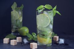 Två exponeringsglas av mojitococtailen med nya limefrukt-, mintkaramell- och iskuber på en mörk bakgrund arkivfoton