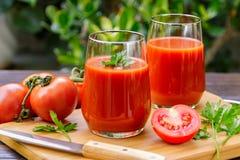 Två exponeringsglas av nya tomatfruktsaft och tomater på en träcutti Arkivfoton